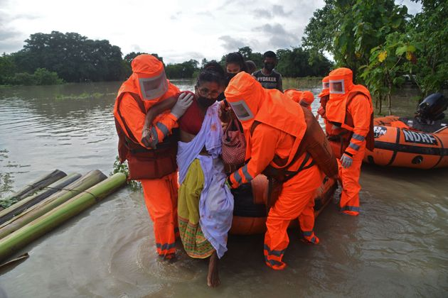 NDRF personnel carry a sick woman during a rescue operation in a flood affected area due to monsoon rains,...