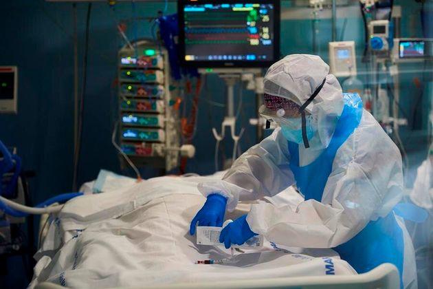 Un profesional sanitario toma una muestra de sangre a un enfermo de la COVID -19 en la UCI del Hospital...