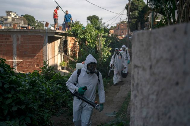 Volunteers spray disinfectant in an alleyway to help contain the spread of the new coronavirus in the...