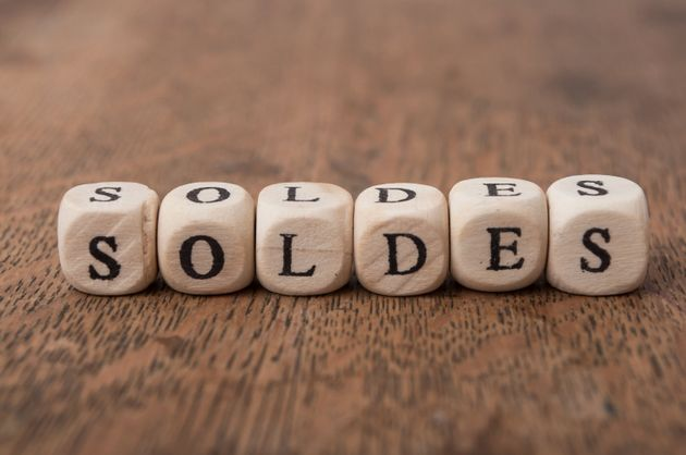 Closeup of word on wooden cube on wooden desk background concept - soldes (discount in
