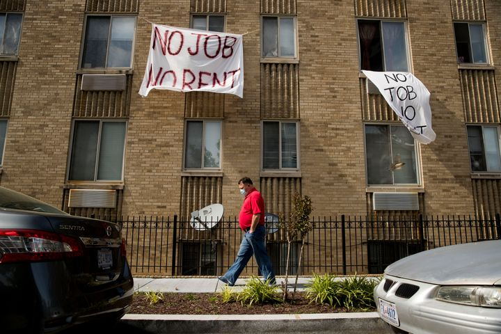 """Signs that read """"No job, no rent"""" hang from the windows of an apartment building in northwest Washington, D.C., in May. The p"""