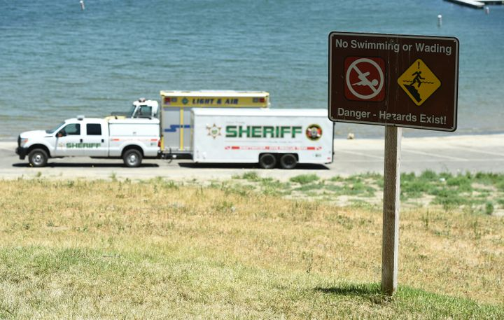 A sign warns of safety hazards as members of the Ventura County Sheriff's Underwater Search and Rescue Team search Thursday for former 'Glee' actor Naya Rivera in Lake Piru, in Southern California.