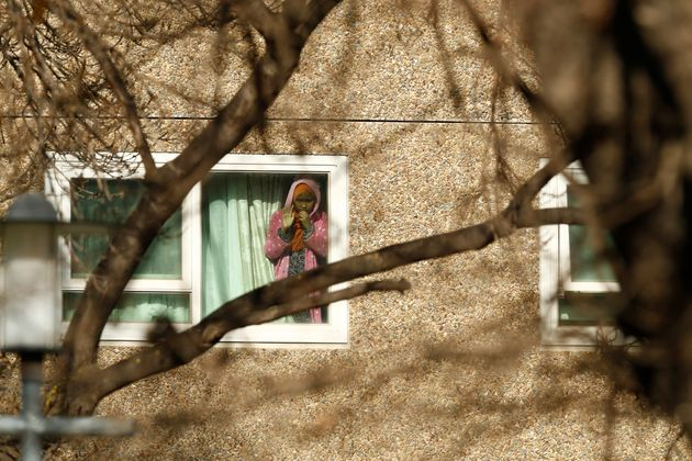 A girl looks out a window of the North Melbourne Public Housing tower complex on July 8. Residents of...
