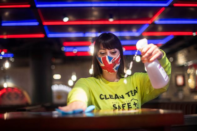 Funcionária do Hard Rock Café desinfecta mesa logo antes da reabertura da unidade no Piccadilly...