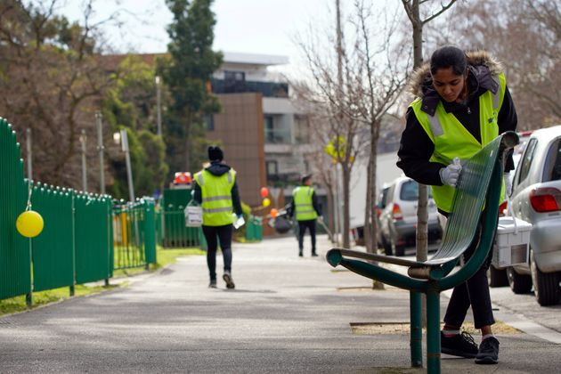 A sanitation worker cleans a bench outside the single remaining public housing tower under a lockdown...