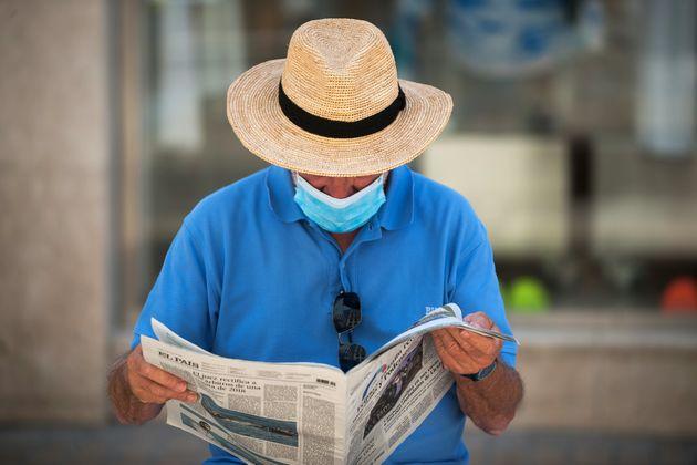 Un hombre lee un periódico con mascarilla y