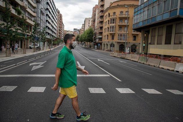 Un vecino de Lleida cruza este domingo una avenida casi vacía, un día antes de que la Generalitat estableciera...