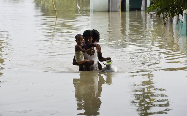 A man carries his children to a safer place in a flood-affected village of Kamrup district of Assam,...