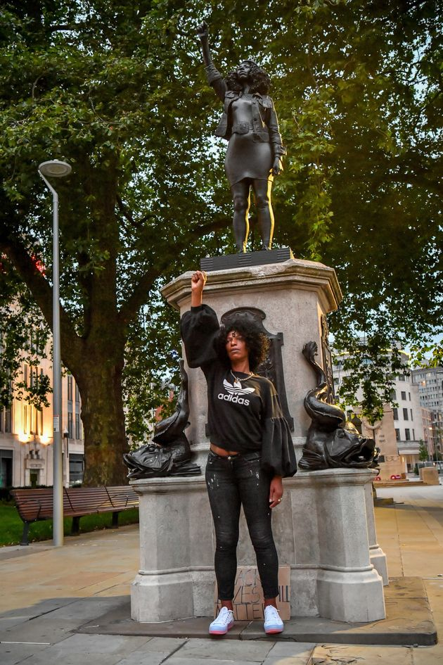 Jen Reid poses in front of her black resin and steel statue titled A Surge of Power (Jen Reid) 2020,...