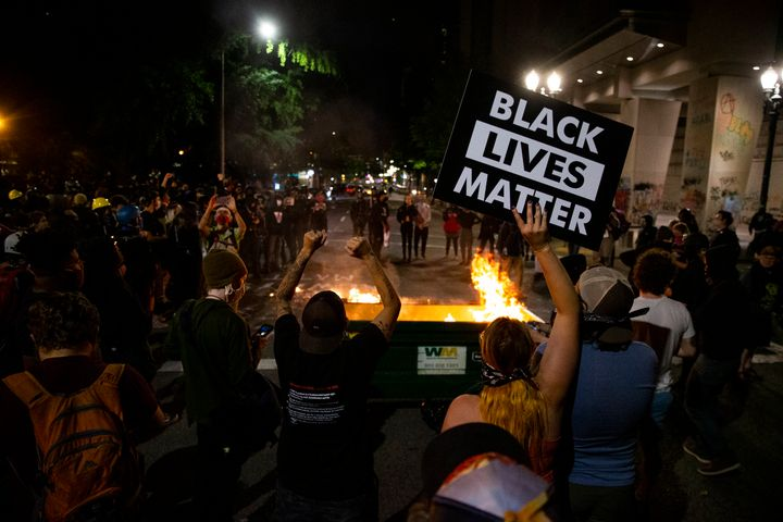 A waste receptacle's contents are in flames as protesters gather in downtown Portland, Ore. on July 10, 2020. The mayor of Po