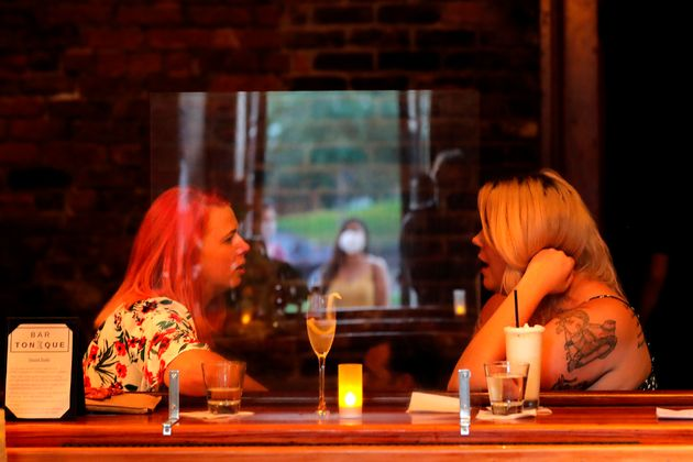 Women chat at bar in New Orleans on July 9, 2020, while a masked woman looks on in the background. Several...