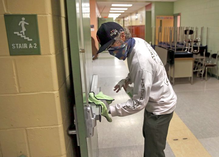 A custodian wipes down a hallway doorway at the Mildred Avenue K-8 School building in Boston ahead of the school reopening la