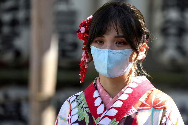 Una mujer con un kimono y una máscara facial protectora visita el Templo Sensoji en el distrito de Asakusa...
