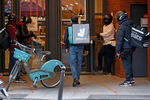 Des livreurs de Deliveroo et Uber Eats attendent de livrer les repas d'un fast-food pendant le confinement...