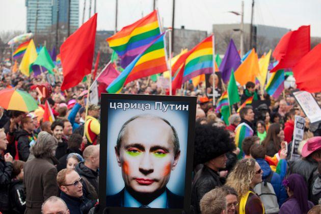 Manifestante segura uma foto que mostra o presidente russo Vladimir Putin com maquiagem e bandeiras LGBT...