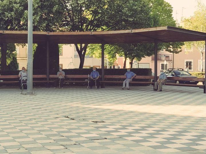 Idosos dão exemplo de distanciamento social em uma praça na Espanha