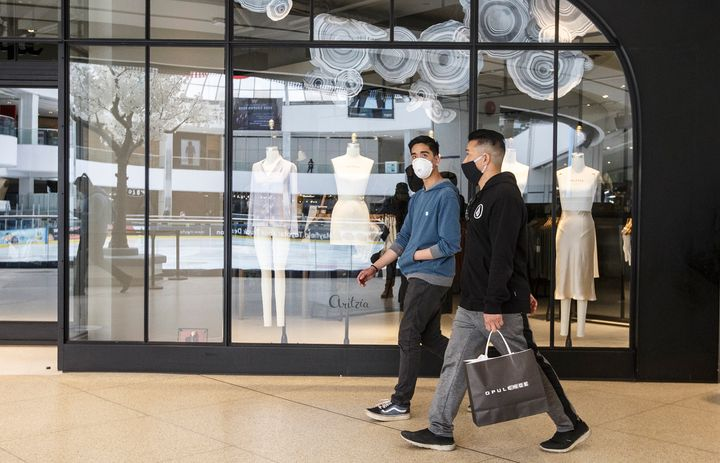 Shoppers walk past stores in West Edmonton Mall in Edmonton on May 14, 2020.