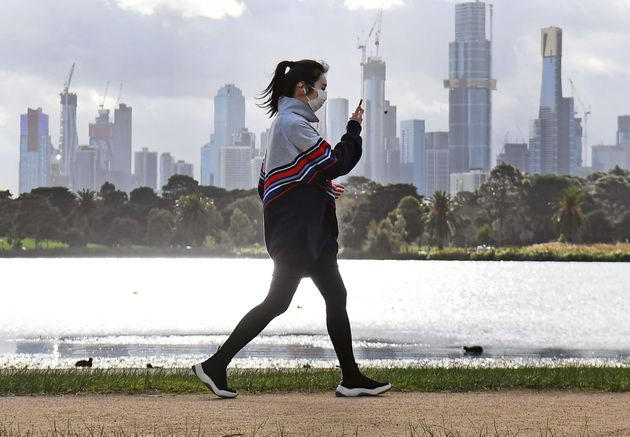 A woman exercises along Albert Park lake in Melbourne on July 13, 2020, as five million people in Australia's...