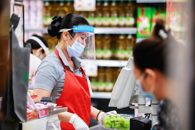 female supermarket cashier in medical protective mask working at supermarket. covid-19 spreading