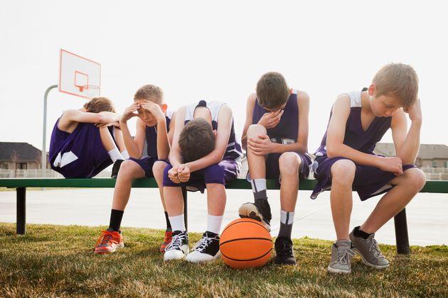 Caucasian basketball team sulking by