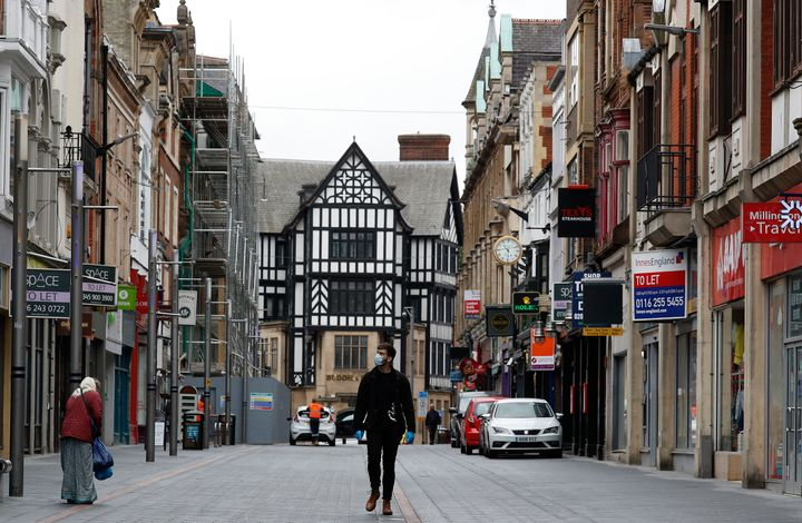 A man walks down a near empty shopping street in Leicester, England, on July 1, 2020. Leicester became the first British city