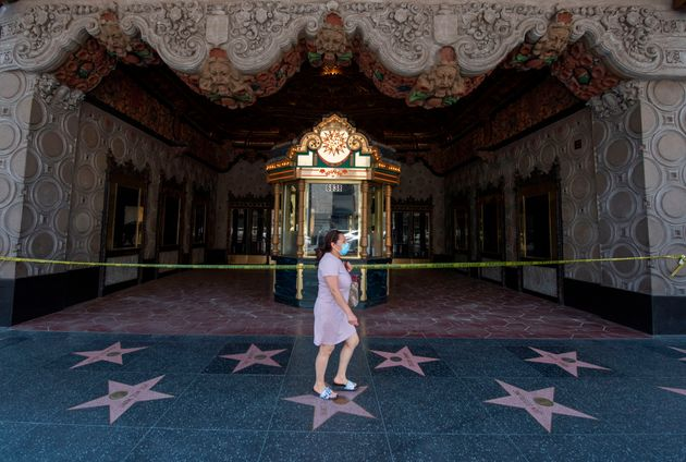 A woman walks past the El Capitan Theater on Hollywood Boulevard in Los Angeles on June 12, 2020. As...
