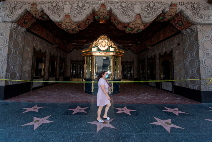 A woman walks past the El Capitan Theater on Hollywood Boulevard in Los Angeles on June 12, 2020. As coronavirus cases in Cal