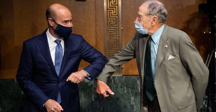 Labor Secretary Eugene Scalia, left, elbow bumps Sen. Chuck Grassley (R-Iowa) before the start of a Senate Finance Committee