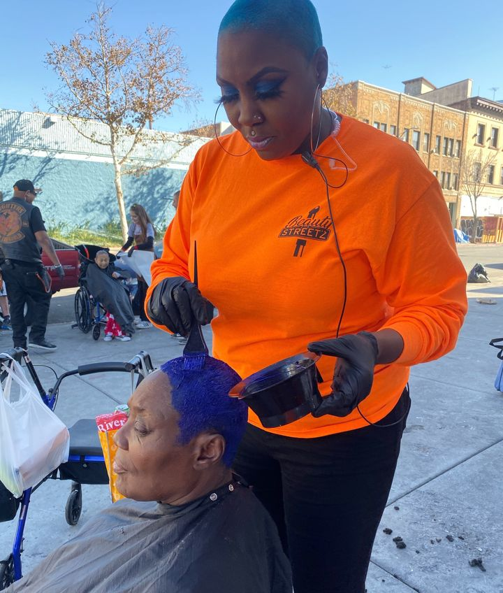 Shirley Raines applies color to a client's hair on the streets of Los Angeles.
