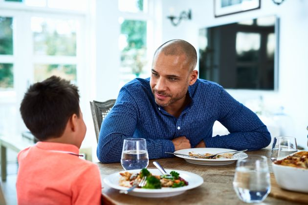 Mature man leaning forward towards boy, food on dining room table, family meal time, conversation, bonding