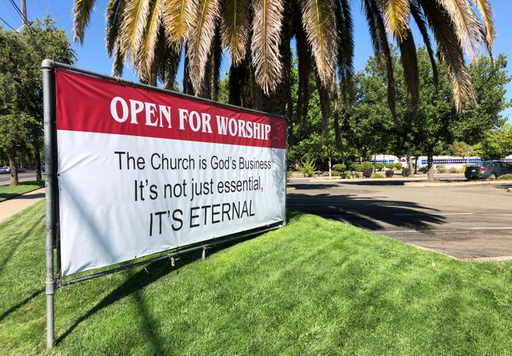 "An ""Open for Worship"" banner is posted July 9 outside the Crossroads Community Church in Yuba City, Calif."