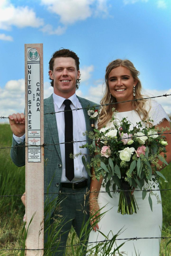 Newlyweds Jaxson (left) and Kadee pose at the Canada-U.S. border where they got married.