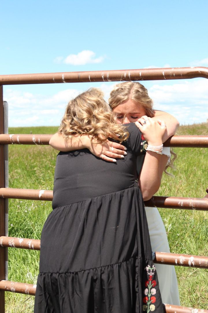 Kadee Jensen hugs her mother through a fence at the Alberta-Montana border on her wedding day.