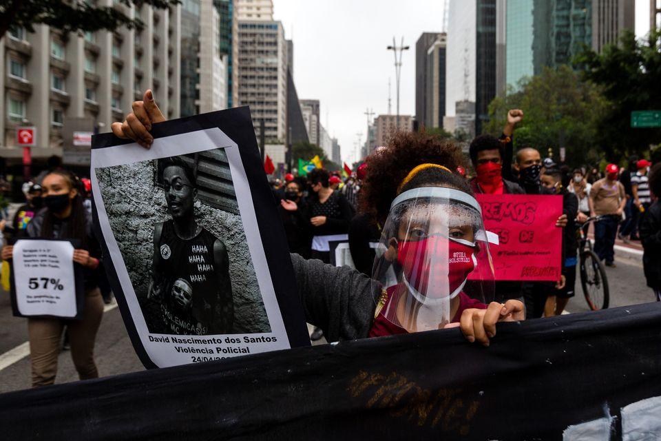 Manifestante segura imagem de jovem vítima da violência policial em protesto na Avenida...