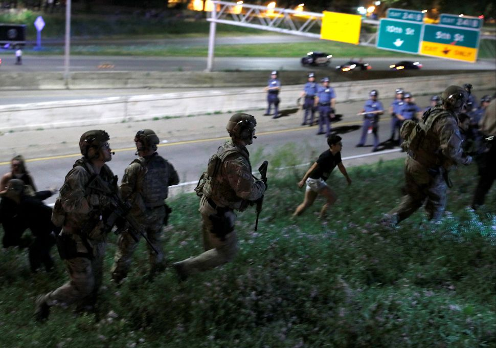 SWAT officers in riot gear chase down police brutality protesters in St. Paul, Minnesota, in June 2017. The increasing aggres
