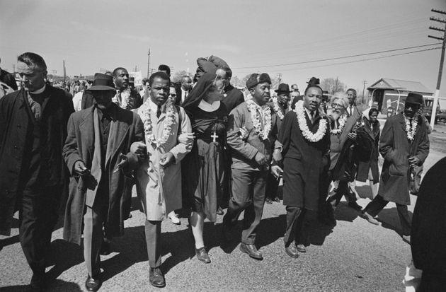 1965년 3월21일, 앨라배마주 셀마의 브라운 채플 교회 앞에서 마틴 루터 킹 주니어 목사와 함께 행진을 시작하는 존 루이스(왼쪽에서 세