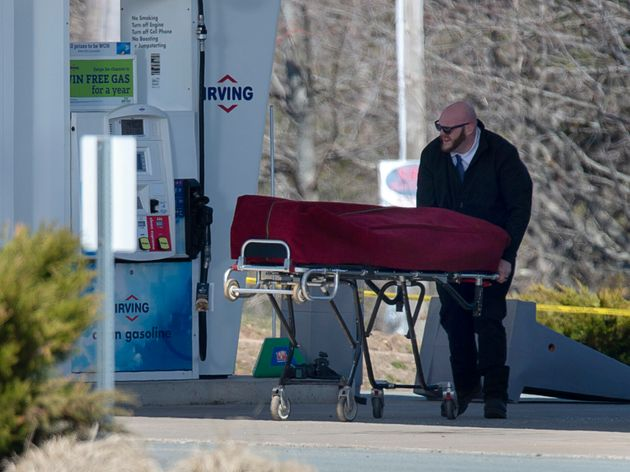 A worker with the medical examiner's office removes a body from a gas bar in Enfield, N.S. on April 19,...