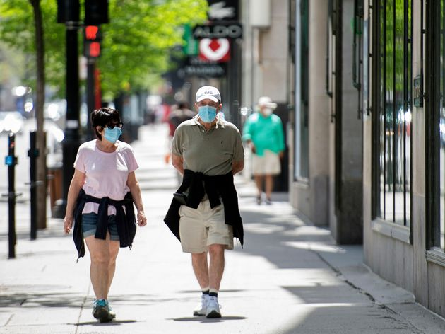 A man and woman wear face masks as they walk along Sainte-Catherine street in Montreal on May 24,
