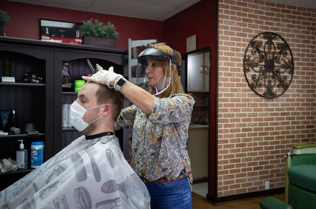 Owner Rosanna Petan wears a face shield and Jack Willis wears a face mask as she cuts his hair at Frank's...