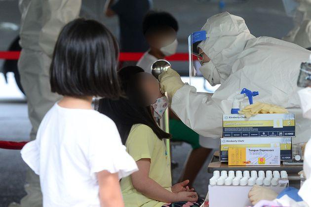 18일 오후 광주 서구의 한 초등학교에 마련된 이동선별진료소에서 학생들이 코로나19 검사를 받고 있다. 앞서 이 학교에 다니는 남매가 코로나19 양성 판정을
