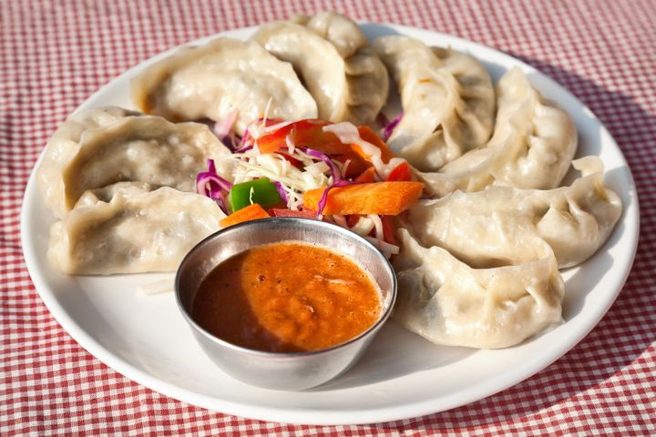 Nepalese traditional dumpling momos served with tomato chatni and fresh salad in restaurant
