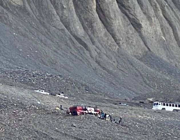 Responders attend to a rolled-over icefield touring bus in Jasper National Park, Alta., in a handout...