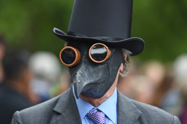 A man wearing a plaque mask attending a protest against the wearing of masks during the coronavirus outbreak,...