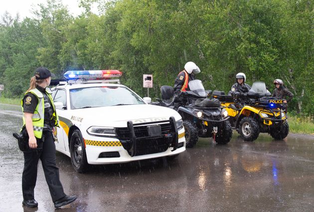 Surete du Quebec officers block the road accessing a search area near Saint-Apollinaire, Que. on July...