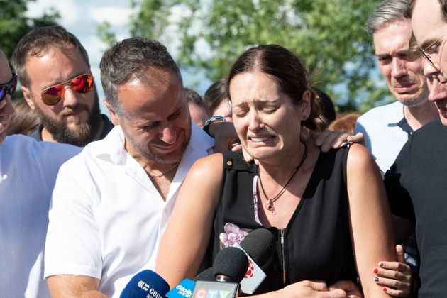 Amelie Lemieux, is comforted by family members as she speaks of her two daughters, Romy and Norah Carpentier,...