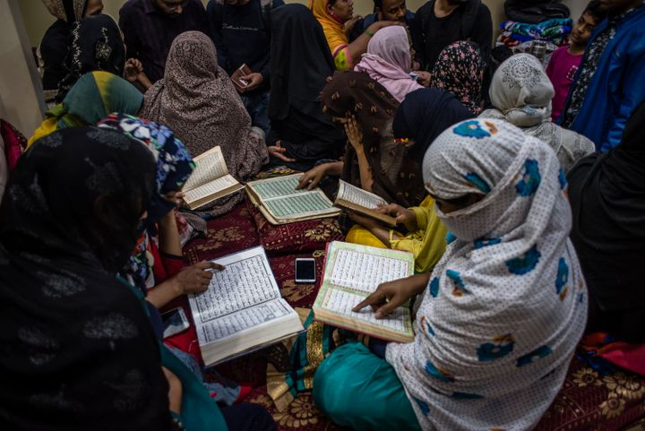 Indian Muslim women riot survivor recite holy Quran as they seek shelter in a makeshift camp, in a riot-affected area on March 01, 2020 in New Delhi.
