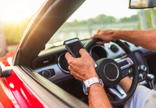 Caucasian man using cell phone and driving