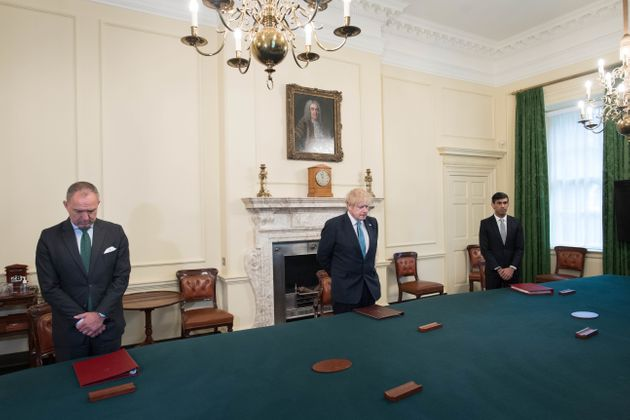 While socially distancing, Boris Johnson (centre) stands with cabinet secretary Sir Mark Sedwill (left)...