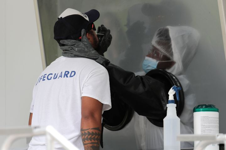 Rafael Ruiz, left, is tested for COVID-19 at a walk-up testing site during the coronavirus pandemic, Friday, July 17, 2020, i