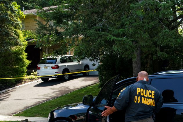 Law enforcement officials are seen July 20 outside the home of U.S. District Judge Esther Salas, where...